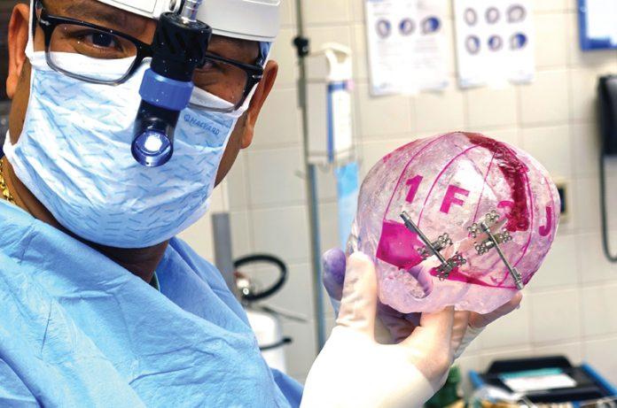 Dr. Kongkrit Chaiyasate holding infant skull