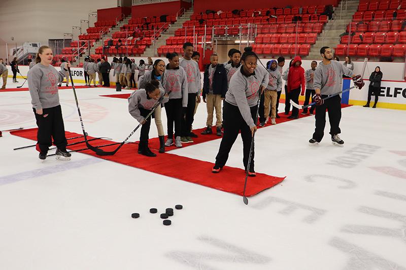 students shooting hockey pucks