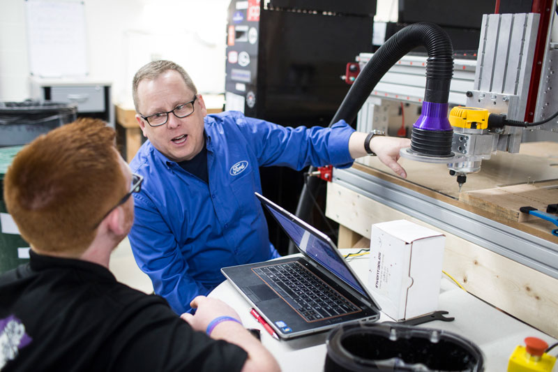 Ford volunteer with FIRST Robotics student