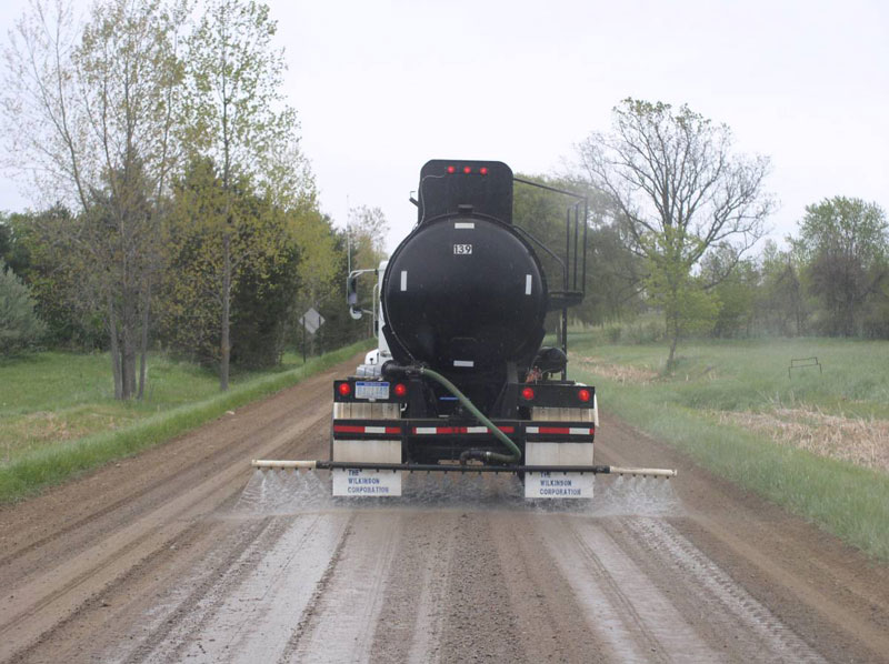 truck treating dirt road withcalcium chloride solution