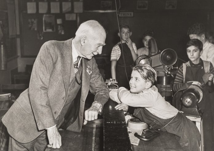 C.S. Mott speaking with child