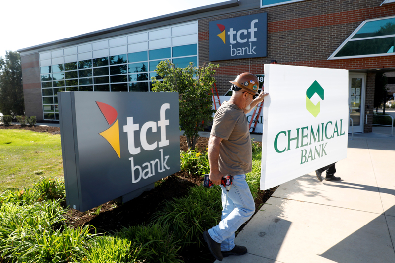workers changing Chemical Bank signs to TCF National Bank signs