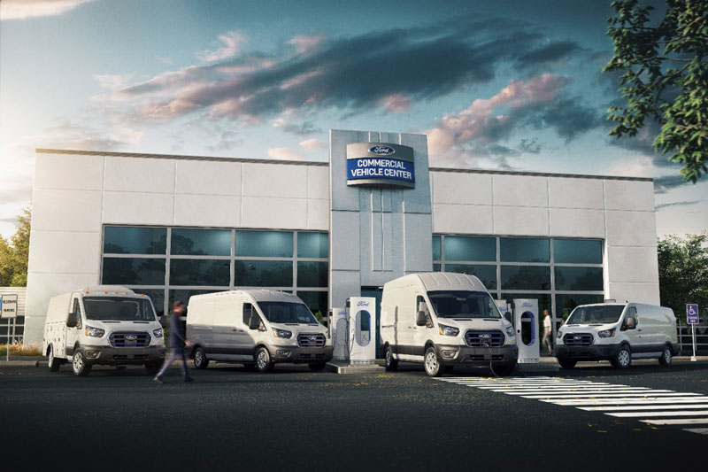 Ford E-Transit vans in front of service center