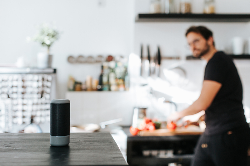 Adult man asks cooking advice from smart speaker