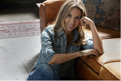 Sheryl Crow leaning on a couch