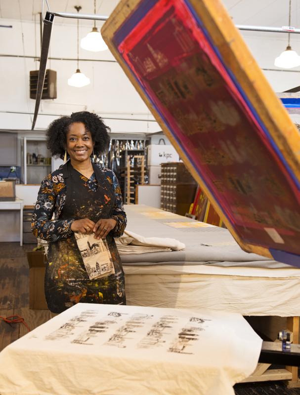 Shayla Johnson standing with printing Equipment