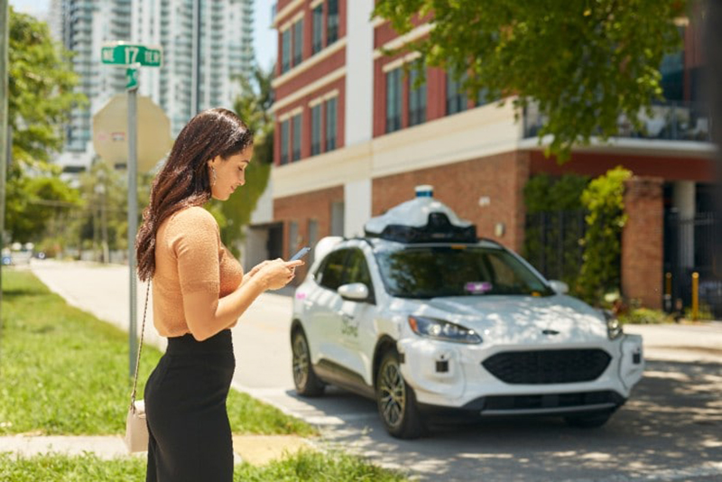 A woman hails an autonomous cab, which will be mobilized at scale in an industry-first collaboration between Ford, Argo AI, and Lyft. // Courtesy of Ford Motor Co.