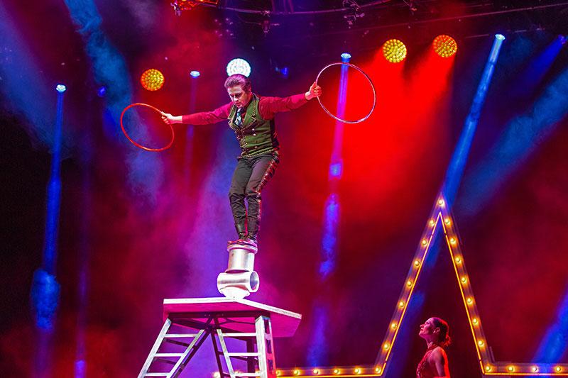 A circus performer balances on a platform