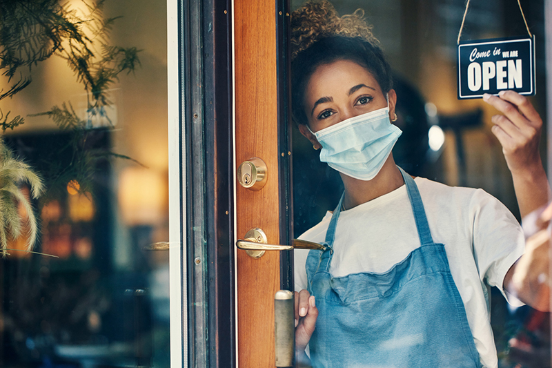 A young masked women in a blue apron flips the open sign in a glass door
