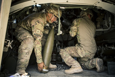 U.S. Army soldiers loading an artillery shell in a Howitzer tank, a process which Eckhart will develop a robotic-assistance system to improve speed and safety. // Courtesy of the Department of Defense