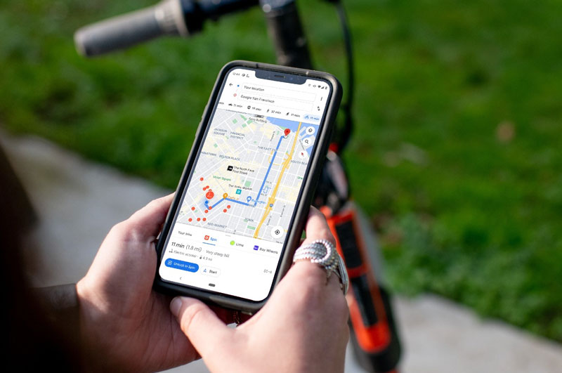 A smartphone displaying google maps being held above a Spin e-scooter