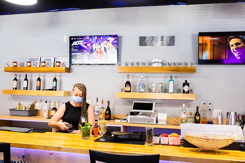 a woman wearing a mask works behind a modern bar