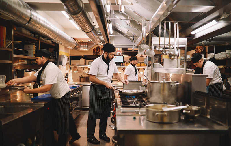 Four cooks in a restaurant kitchen working at different stations