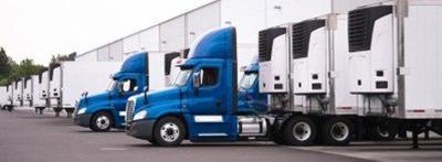 Semi trucks parked at a loading bay at a warehouse