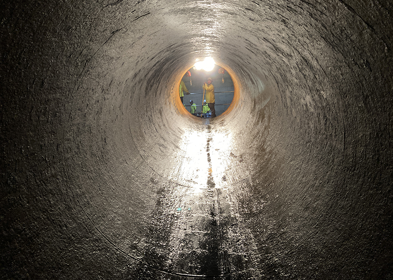 A man standing at the end of a large pipe