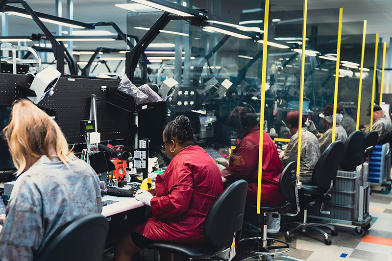 factory workers at a weapons optics manufacturing plant