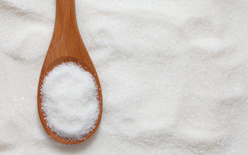 wooden spoon full of sugar on a sugar background