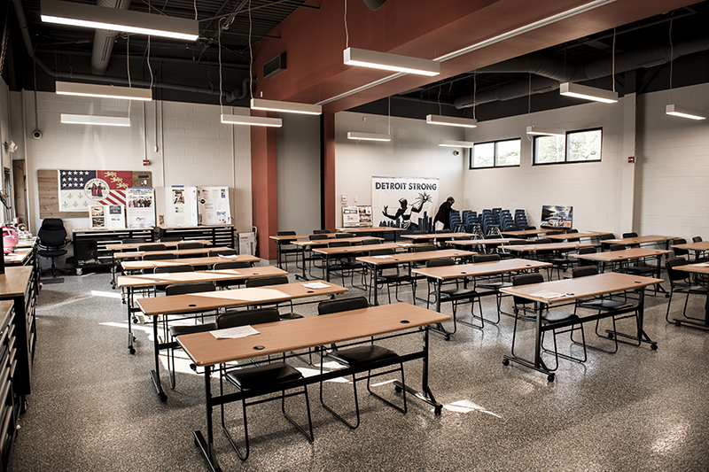 a classroom with rows of two-seat tables, someone picks up chairs in the background