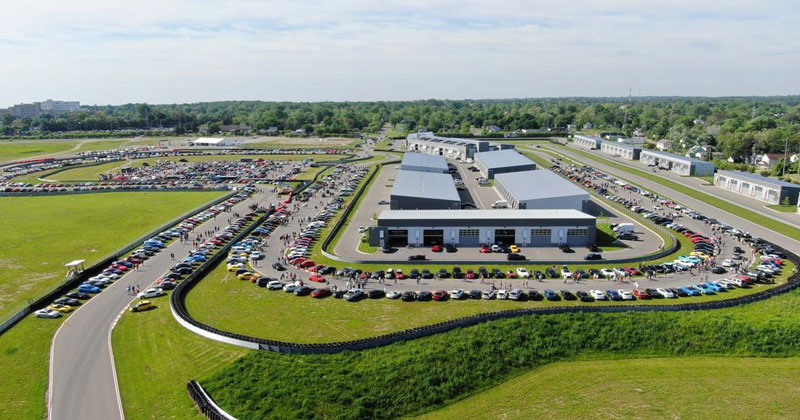 An aerial shot of the M1 Concourse in Pontiac with cars on display lining the track around the garage.