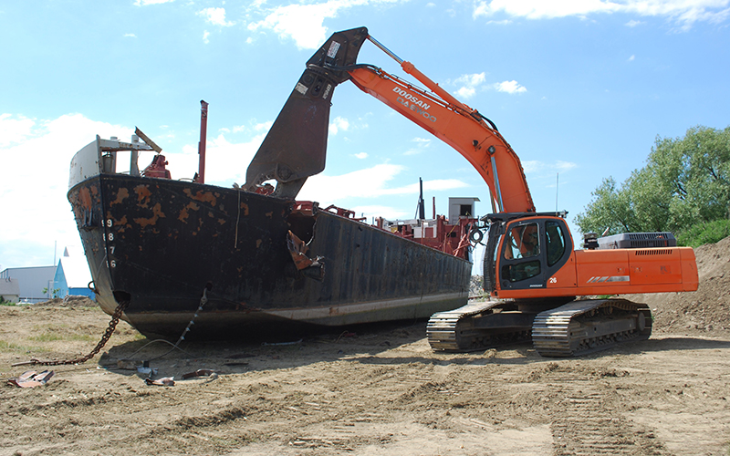 A backhoe reaching into a dumpster on a construction site