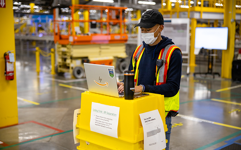A man works on a laptop at an amazon fulfillment center