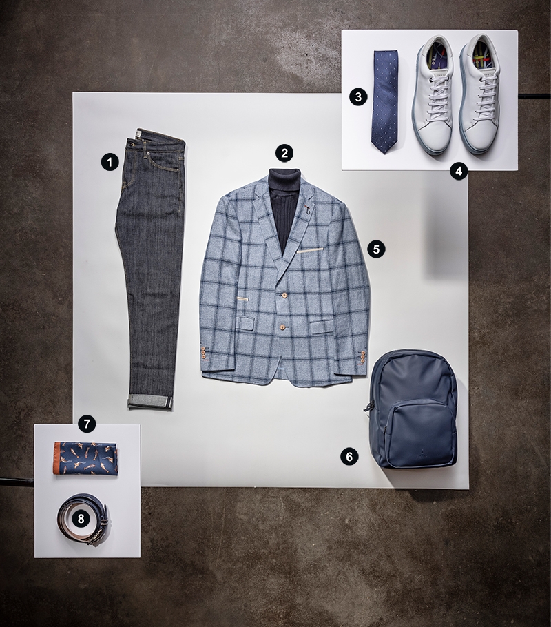 a stylized fashion layout. In the bottom left are a leather belt and orange and navy fish print pocket square. Up and right from that is a pair of dark jeans, a black turtleneck surrounded by a blue checked blazer, and a plain navy backpack. Up and right from that is a navy tie with a dot pattern and a pair of white sneakers.