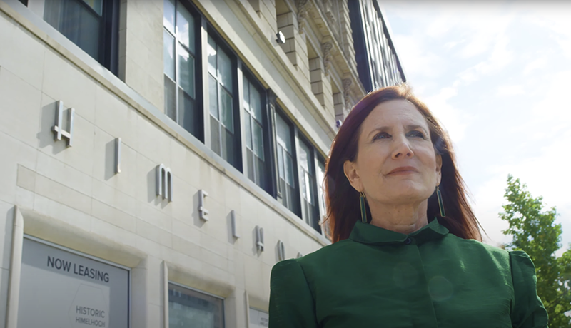 Carol Himelhoch stands in front of the company's former bricks-and-mortar location just south of the David Whitney Building, which has since been converted into a residential and commercial development. // Courtesy of In Good Co. Detroit