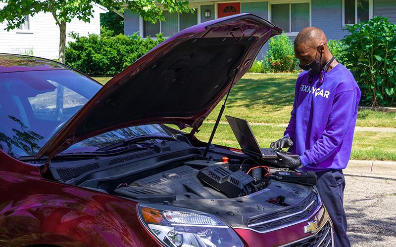 A FixMyCar technician working under the hood on a service call. // Courtesy of FixMyCar