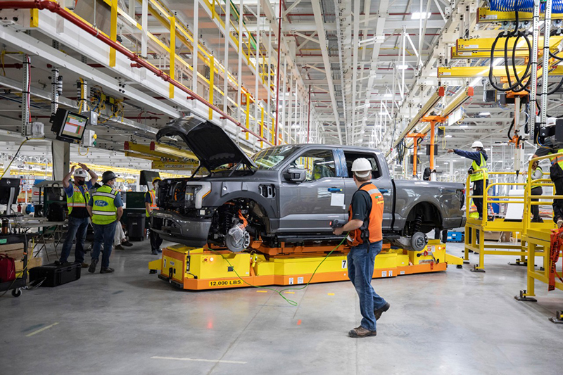 workers on an assembly line with a pre-production F-150 lightning