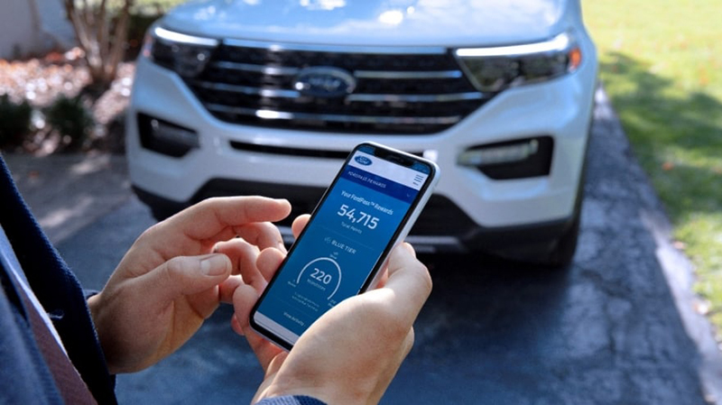 Someone of the FordPass Rewards app in front of a Ford SUV