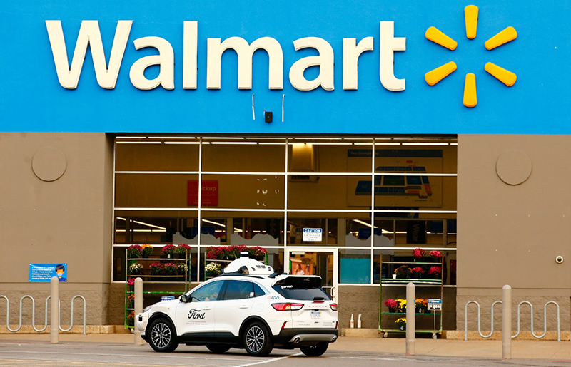 a ford car equipeed with argo ai wait outside a walmart to make a delivery