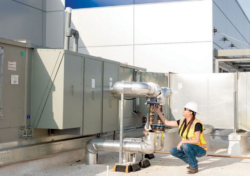 a man in construction garb squats near an industrial heating and cooling unit