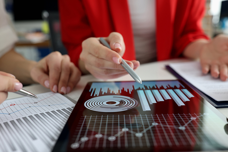 Business women studying charts and diagrams on digital tablet closeup