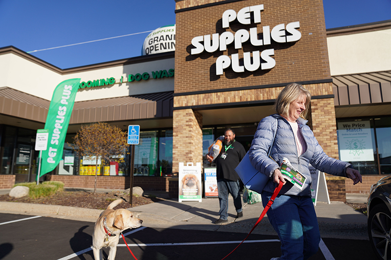 a woman leaving a pet supplies plus store with her dog on a leash. An employee follows carrying her purchases