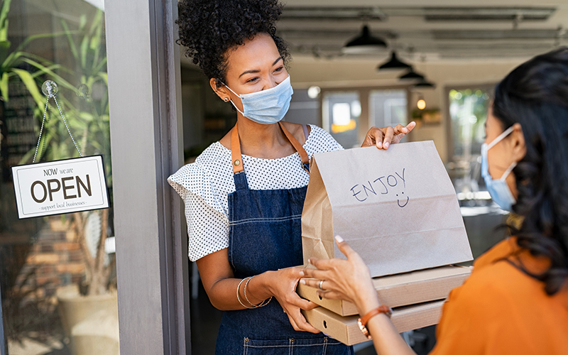 African restaurant owner working only with take away orders during corona virus outbreak. Young black woman wearing face mask giving takeout meal to customer outside her cafeteria. Customer pick up take-away food ordered at home, support local small business during covid19 pandemic.
