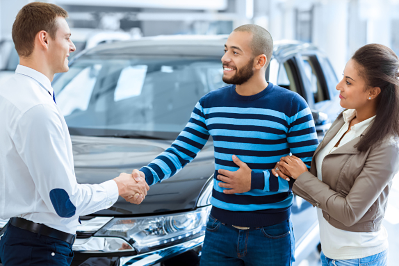 two people shaking hands with car salesman