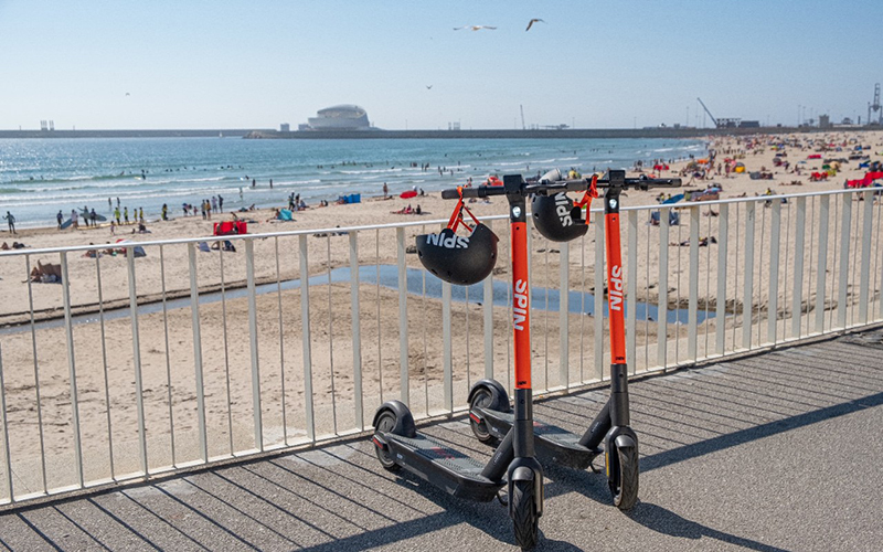two e-scooters on a boardwalk with a beach in the background