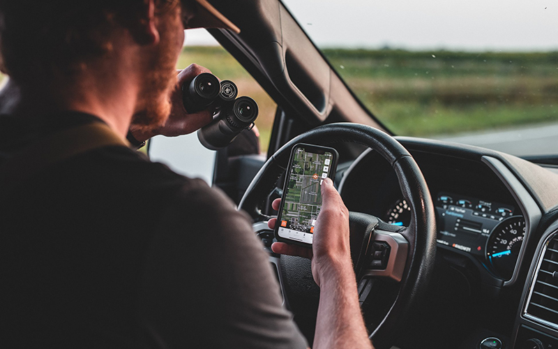 a man holds a cell phone in his right hand and binoculars in his left in the front seat of a truck, scouting for deer