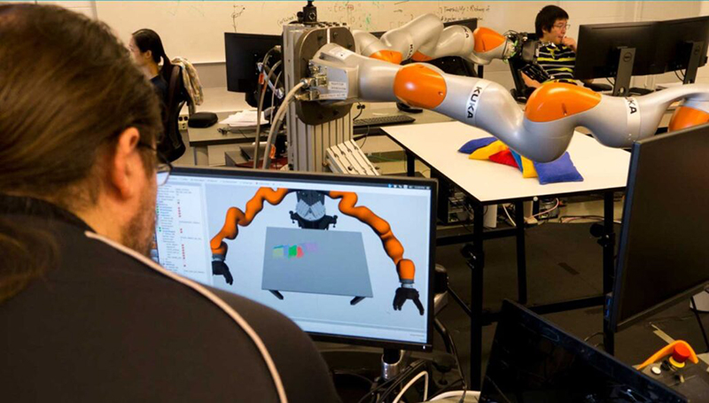 A U-M graduate student operates a KUKA robot similar to the ones used in the $2 million study. // Courtesy of the University of Michigan