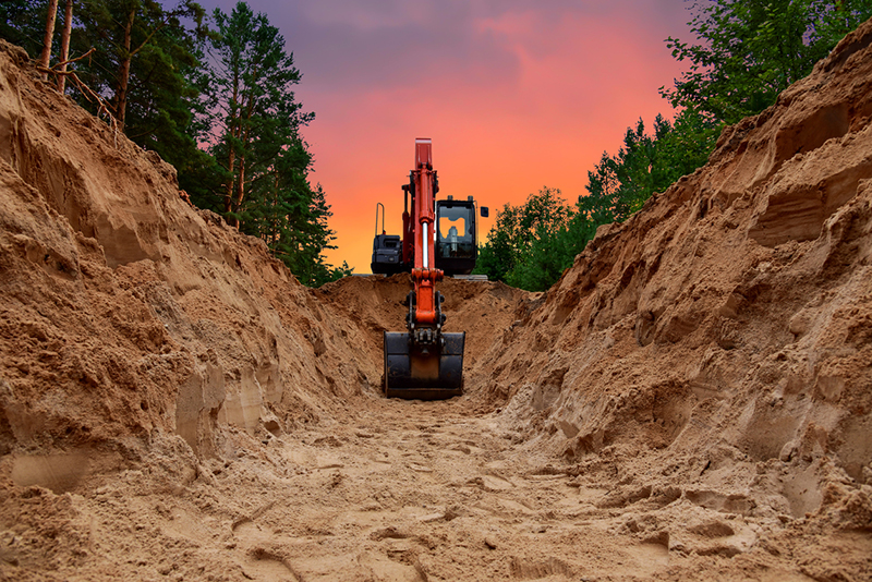 Excavator dig trench at forest area on amazing sunset background