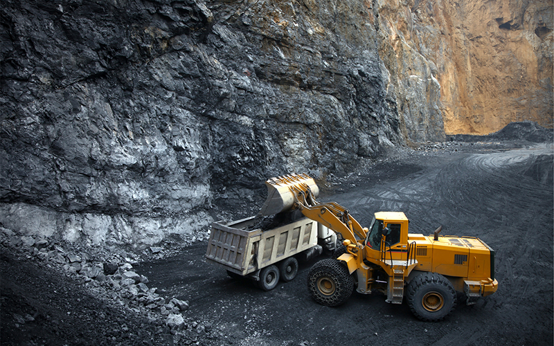 a back hoe dumping mined material into a truck at the bottom of a pit mine