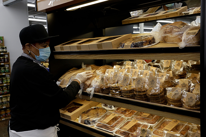 an employee arranges fresh-baked bread in a display