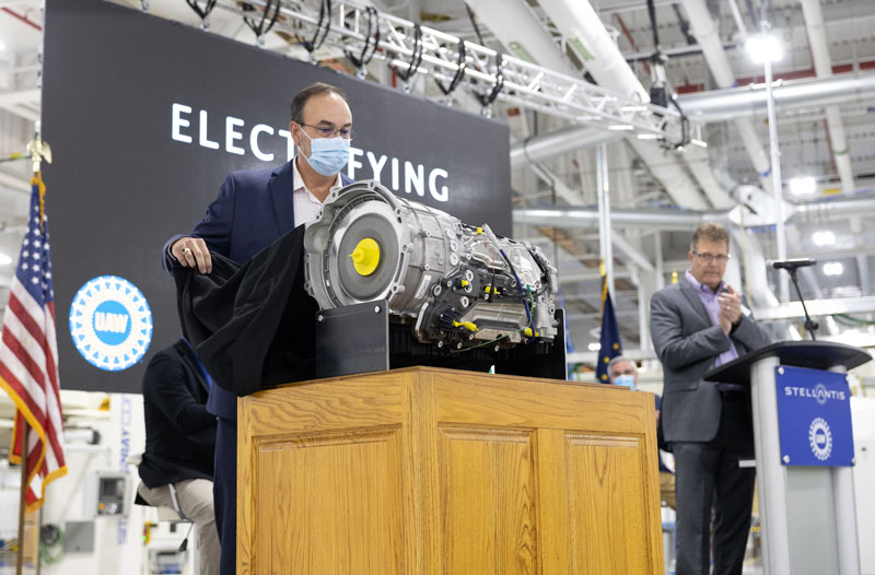 Dave Dukes, head of transmission operations for Stellantis pulls the cover off the automaker's new, electrified, fourth-generation, eight-speed transmission at its Kokomo Transmission plant in Indiana. // Courtesy of Stellantis