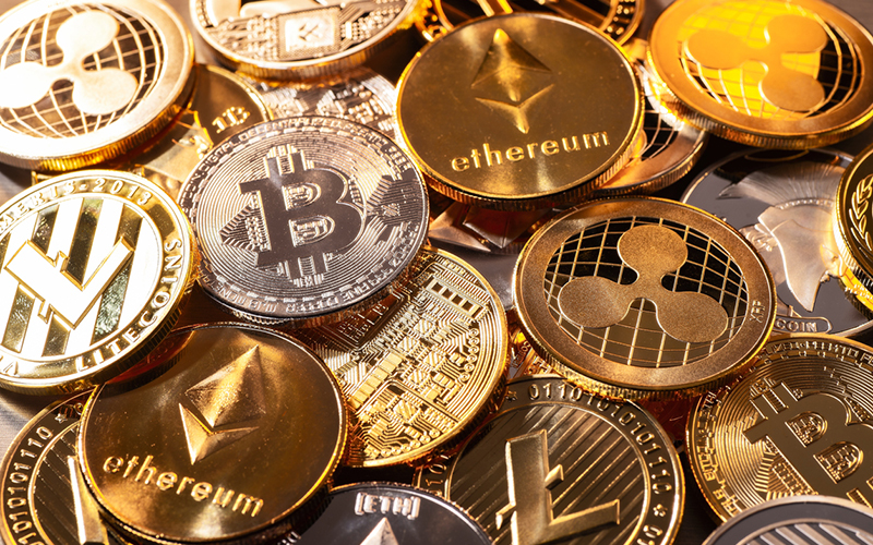 a pile of gold coins with cryptocurrency logos